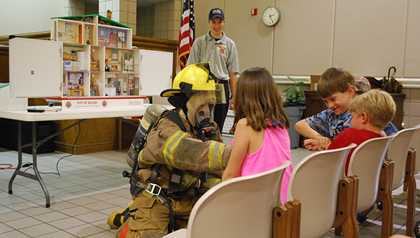 A Helena Fire Explorer dresses up in a complete fire suit to show kids attending the summer reading program what it's like to be in full uniform. (Reporter Photo/Graham Brooks)