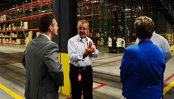 Hibbett Vice President of Distribution Tony Lago, center, gives a group of visitors a tour of the company's 420,000-square-foot facility in Alabaster on June 4. (Reporter Photo/Neal Wagner)