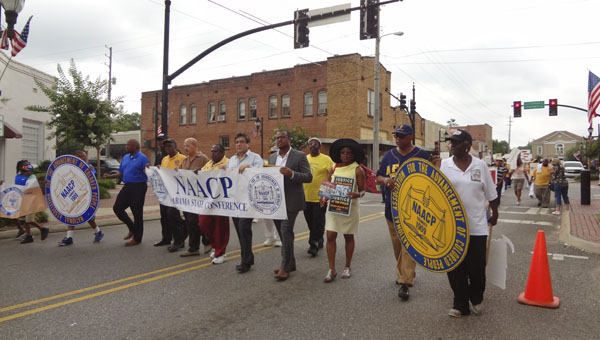 """Dozens of people participated in the Alabama State Conference of the NAACP's first """"Restore our voting rights rally and march"""" on June 20 in downtown Columbiana. (Reporter Photo/Emily Sparacino)"""
