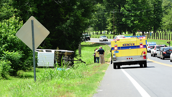 Columbiana police and Southeast Shelby County Rescue paramedics speak with the driver (center, yellow shirt) of the overturned white Chevrolet pickup at about 2:10 p.m. on July 9 on Shelby County 26. (Reporter Photo/Neal Wagner)