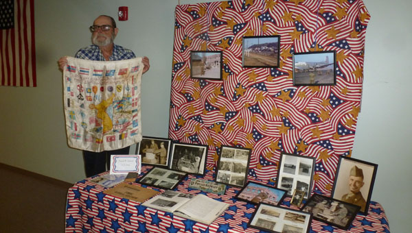 Army Veteran Don Gothard of Columbiana holds a silk hand-painted map of Korea which also displays the military units and countries involved in the Korea War at his display table in the Hall of Memories at the First Baptist Church of Columbiana on Liberty Day. Gothard bought the silk during his 16-month tour on the DMZ 38th Parallel at No Man's Bridge between North and South Korea in 1954-1955. (Contributed)