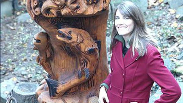 Heather Bailey with her favorite piece, a 20-foot-tall wildlife totem pole. (Contributed)
