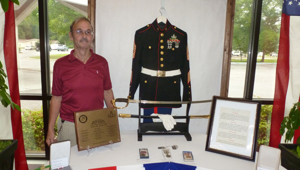 Master Sgt. Brian Crumpton, U.S. Marine Retired, stands beside his Marine dress uniform at his military display at the Hall of Memories at the First Baptist Church of Columbiana on Liberty Day. (Contributed)