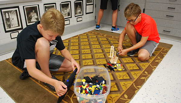Upcoming sixth grader Aaron Surcouf (right) tests his completed excavator project to see how it works on Wednesday, July 8, at HIS during a Camp Build Enrichment Camp. (Reporter Photo/Graham Brooks)