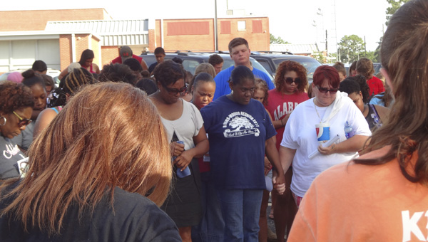 People gathered in the Shelby County High School parking lot pray for Haleigh Green, a local 18-year-old who went missing on July 7. (Reporter Photo/Emily Sparacino)