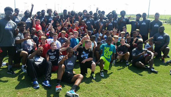 Members of the Alabama Prep Sports Academy pose for a picture with kids from the Calera parks and rec department. (Contributed)