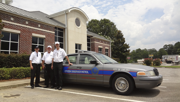 Chelsea COP members Bob Bush, Robert Everett and Donald Shirley stand next to the latest COP patrol car acquisition, a Ford sedan the county donated to the city about three months ago. (Reporter Photo/Emily Sparacino)