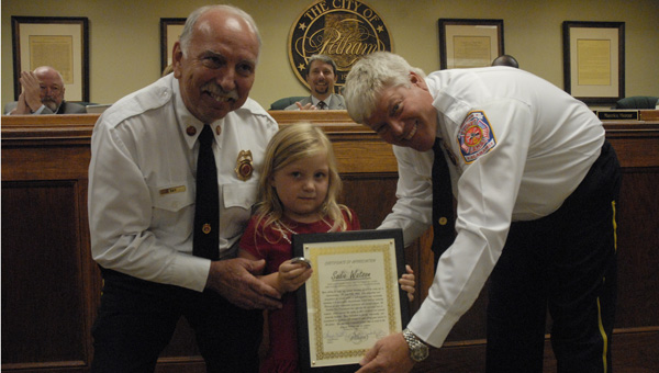 Fire Chief Danny Ray and Deputy Chief Blair Sides present Sadie Watson with a certificate of appreciation to thank her for her assistance with a fire. (Reporter photo / Jessa Pease)