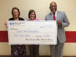 Blue Cross Blue Shield representative Jeff Adams, right, presents a grant to Creek View Elementary Principal Charissa Cole, left, and teacher Abbey Tipton, center. (Contributed)