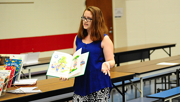Thompson High School junior Tabitha Lawler presents 65 Spanish-language books to the Creek View Elementary School library on Aug. 12. (Reporter Photo/Neal Wagner)