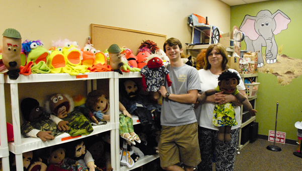 Christopher Robinson and Anita Hardy display some of the puppets used in Steppup, a puppet ministry at North Shelby Baptist Church. (Reporter Photo/Emily Sparacino)