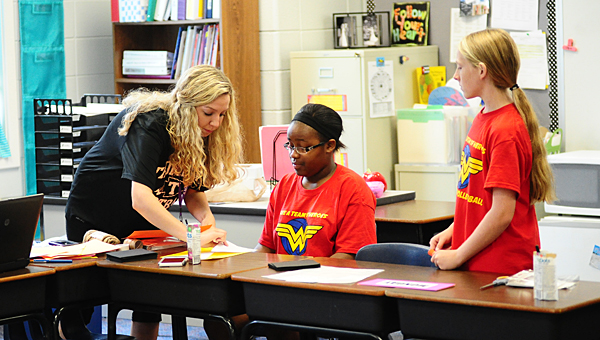 Thompson Middle School volleyball players Dreka Caffey, center, and Kaylee Cannon, right, help Meadow View Elementary School teacher Lindsey Thigpen prepare for the first day of school during an Aug. 7 visit. (Reporter Photo/Neal Wagner)