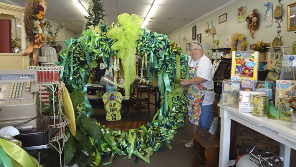 Main Street Florist owner Susan Conn stands next to one of three large wreaths she and volunteers made using green bows residents had displayed in memory of Haleigh Green. (Reporter Photo/Emily Sparacino)