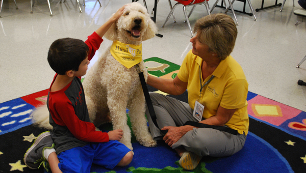 A student pets Simon during a visit to OMES. Simon and fellow therapy dog, Max, often stop by classrooms to greet students during their visits. (Reporter Photo / Molly Davidson)