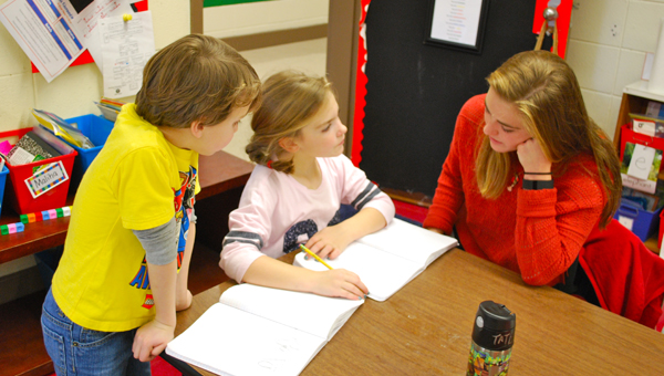 First graders Tate Ronilo and Ally Ross work through a math game with OMHS mentor Julia Buckner. (Reporter Photo / Molly Davidson)