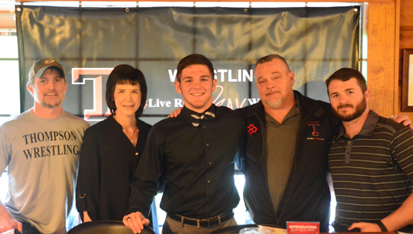 Hank Turner, center, surrounded by his parents and Thompson wrestling coaches Shawn Weltzin, far left, and Chris Pike, far right, pose for a picture on April 20. Turner will continue his wrestling career at Shorter University. (Reporter Photo / Baker Ellis)