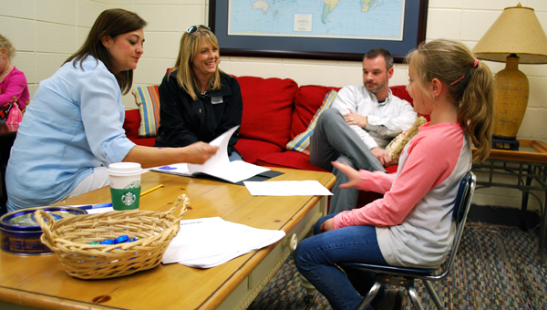IES third grader Rylie Campbell shares her schoolwork and progress with her parents during a student-led conference on April 15. (Reporter Photo/Molly Davidson)
