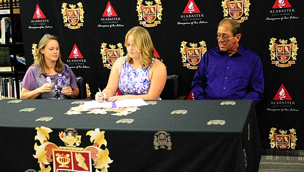THS senior Sarah Owen, while surrounded by her parents, signs a track and field scholarship with the University of Montevallo during an April 27 ceremony in the school's library. (Reporter Photo/Neal Wagner)