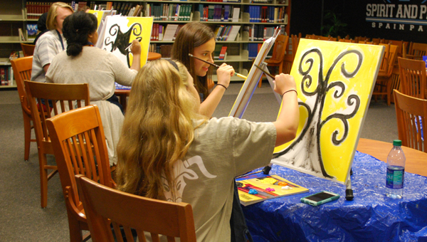 """Students paint at the Spain Park library on April 13 during a """"sips and strokes"""" style program. (Reporter Photo/Molly Davidson)"""