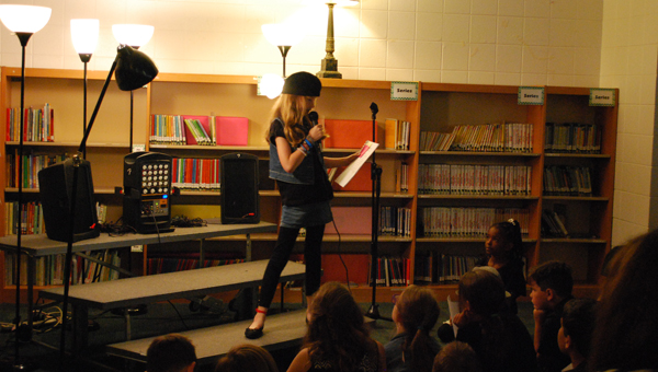 """OMES third grader Leslie Ann reads her poem """"Once I Heard"""" during the Poetry Cafe held in the school library on April 15. (Reporter Photo/Molly Davidson)"""