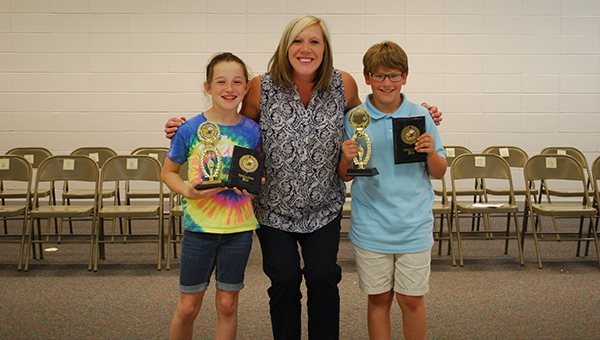 From left, HIS Spelling Bee runner-up Sydney Risch shows off her awards with Laura Sparks and HIS Spelling Bee champion Braden Sullivan. (Reporter Photo/Graham Brooks)