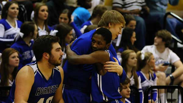 Stephen and Aaron Washington share a moment on the sideline of a Chelsea basketball game.