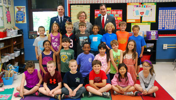 Air Force Lt. Col. Bill Lussier, Carol McLaughlin and Rep. Gary Palmer, R-Alabama, stand with McLaughlin's Greysone Elementary School second grade class. (Reporter Photo/Molly Davidson)