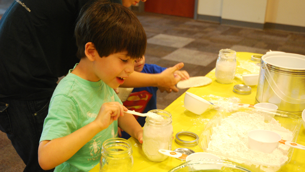 Library scientist Logan mixes together sourdough bread starter during a May 11 Science of Bread program at the North Shelby Library. (Reporter Photo/Molly Davidson)