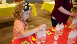 Hannah adds sugar to water in an experiment to see how yeast makes bread rise on May 11. (Reporter Photo/Molly Davidson)