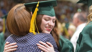 Students file through the teacher tunnel, allowing them to embrace the faculty members before stepping onto the stage.