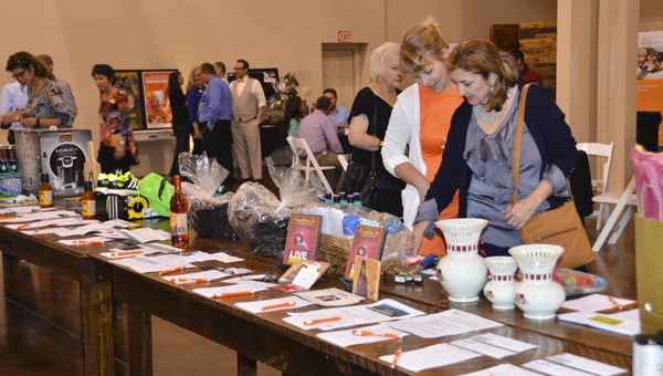 People peruse items in the 2016 Boots and Bow Ties silent auction hosted by the South Shelby Chamber of Commerce at Douglas Manor on April 28. (Reporter Photo/Emily Sparacino)