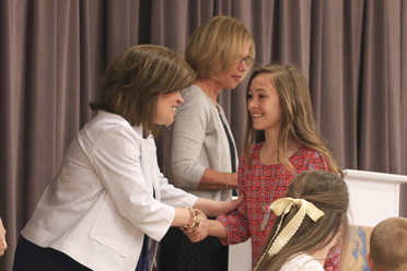 FOES Principal Sasha Baker congratulates a student at the Fifth Grade Awards Ceremony held May 13 in the cafeteria. (For the Reporter/Dawn Harrison)