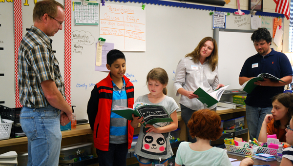 A student in Pam Taylor's third grade class reads a poem to engineer Matt Stoops. Taylor's class wrote thank you letters and poems to each of the engineers they worked with this year. (Reporter Photo/Molly Davidson)
