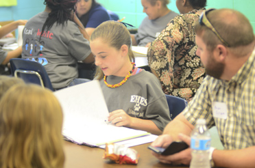 A student shows visitors her leadership notebook at Elvin Hill Elementary School's Leadership Day. (Reporter Photo/Emily Sparacino)
