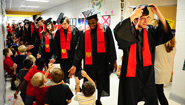 Thompson High School seniors don their caps and gowns as they greet students at Meadow View Elementary School during the parade of graduates event on May 6. (Reporter Photo/Neal Wagner)