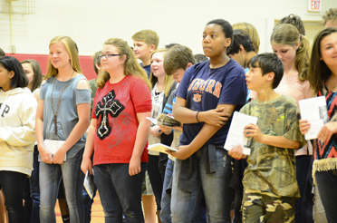 Columbiana Middle School seventh graders hold their published anthologies at a May 10 assembly marking the completion of the Writing Our Stories program. (Reporter Photo/Emily Sparacino)