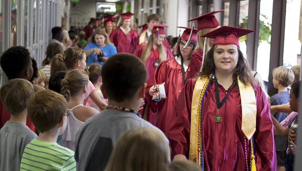 Shelby County High School's class of 2016 greets students in the hallway at Elvin Hill Elementary School during the first SCHS Senior Walk on May 19. (For the Reporter/Kevin McKee)