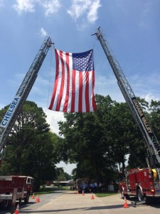 Fire departments from multiple counties and cities came out to celebrate the life and service of Thomas Zopfi IV at his funeral service June 17. Chelsea and Cahaba Valley fire trucks share a giant American flag to honor Zopfi at the cemetery in Vincent. (Contributed)