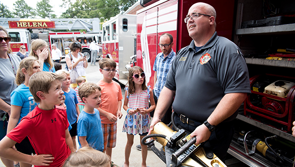 Helena Fire Department Lt. Heath Bartlett (right) shows summer reading participants the Jaws of Life tool during the department's visit to the summer reading program on June 29. (Reporter Photo/Keith McCoy)