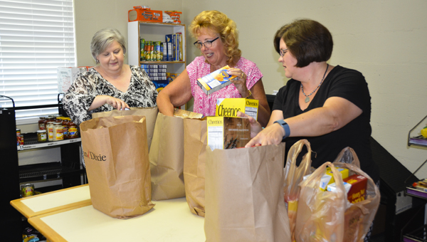 Joan Garrett, Janet Shaw and Pastor Melissa Patrick pack grocery bags for the Chelsea Community Food Table at Lesters Chapel United Methodist Church. (Reporter Photo/Emily Sparacino)