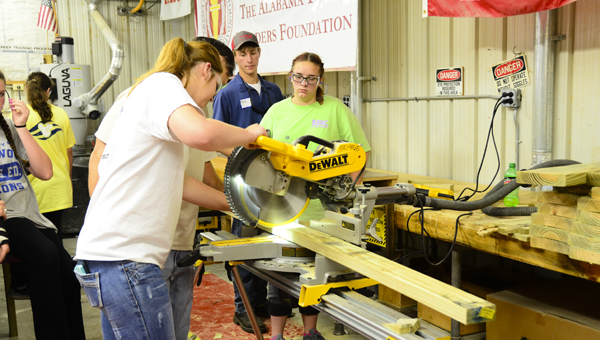 A student uses an electric saw to cut through a piece of wood at the 2016 Girls Can Construction Camp at the Shelby County College and Career Center in Columbiana on June 9. (Reporter Photo/Emily Sparacino)