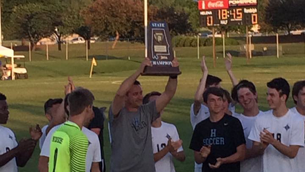 Helena boys soccer head coach Zach Morgan (center) hoists the state championship trophy after Helena defeated Randolph 4-0 for the 4A-5A state championship on May 13. Morgan was awarded Coach of the Year by the NSCAA. (Contributed)