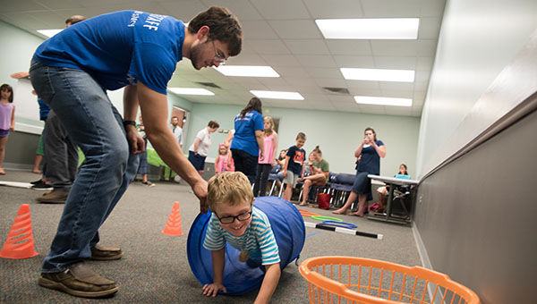 A Helena summer reading program participant weaves through the obstacle course at the Alabamians in the Olympics interactive program on June 22. (Reporter Photo/Keith McCoy)