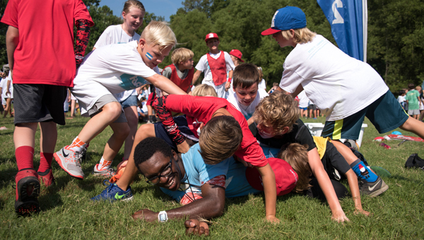 Campers celebrate by piling on their group leader after their group won a game July 21 at WinShape summer camp hosted by Double Oak Community Church. (Photos by Keith McCoy)
