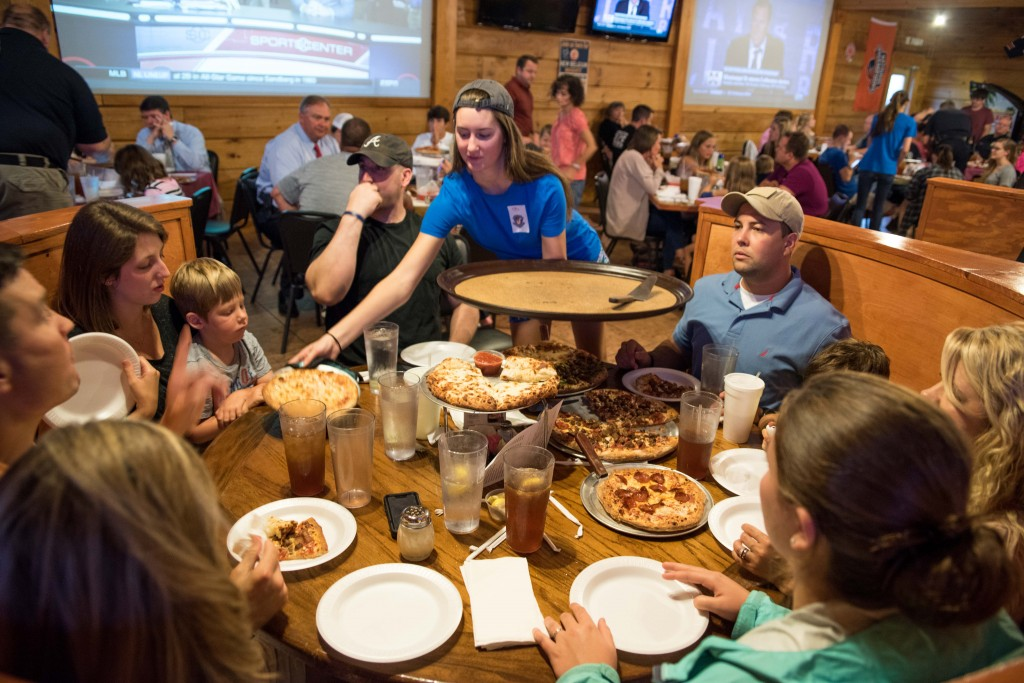 A waitress serves food to Alabaster Police Officers Gonzalez, Harrleson, Houser and their families at a dinner to support the police department on July 11. The meal was free to the officers and their families, made possible by donations from residents and local businesses.