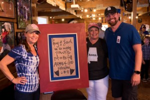 Event organizers Dena Bedsole (left) and Kim Kielbasa stand with Buck Creek Pizza and Wings owner Hunter Spradlin stand in front of a sign welcoming the officers into the restaurant. (Reporter photo/Keith McCoy)