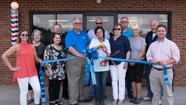 The Barber Shop owner Faye Pray, center, trades her hair scissors temporarily for larger scissors to cut the ribbon on her first day of business July 5 in a South Shelby Chamber of Commerce ribbon cutting ceremony. (Reporter Photo/Keith McCoy)