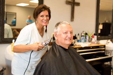 The Barber Shop owner Faye Pray, left, prepares to give Chelsea Mayor Earl Niven a haircut. (Reporter Photo/Keith McCoy)