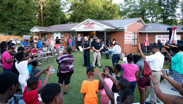 Cutline: Residents praying for the police and community at Kids First Awareness Community Center encircle Alabaster Police Department officers at a prayer night July 26. (Reporter Photo/Keith McCoy)