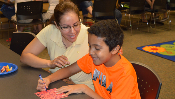 A student celebrates with his mother after winning the first bingo of the day at the Pelham Public Library. (Contributed)